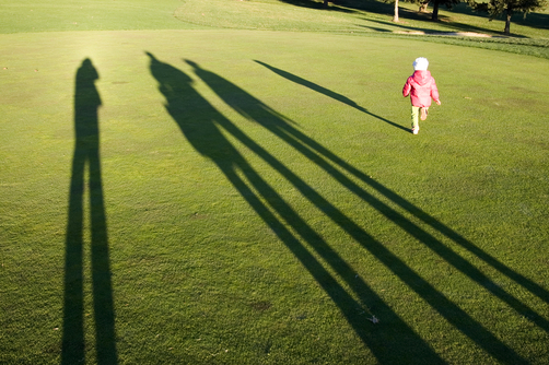 Tall shadows loom on golf course greens as a little girl runs for fun.